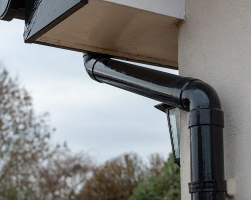 Detailed view of a newly painted gutter and down pipe drainage system seen together with part of a security lantern at the porch of a large house during winter.