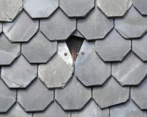 Close up of grey slate roof with missing shingle